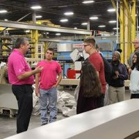 employee showing students around the manufacturing plant
